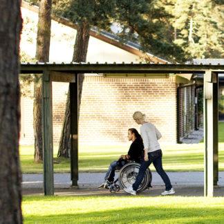 Två personer promenerar på Furubodas område. Den ena använder rullstol och går lite framför den andra.