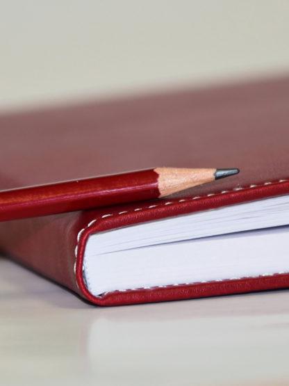 En del av en röd anteckningsbok med en blyertspenna liggande på.