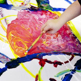 En hand håller i en pensel och målar på en färgglad målning