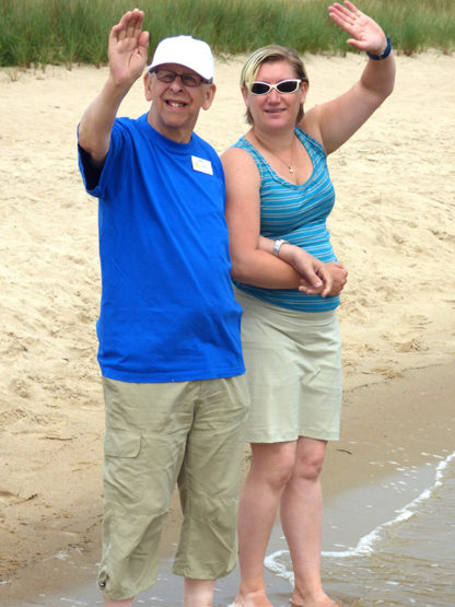 En man och en kvinna står armkrok på stranden med fötterna i vattnet och vinkar glatt