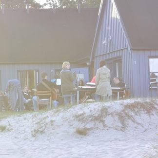 Den blåa Strandstugan med stranden i förgrunden och utanför Strandstugan skymtar människor som umgås.