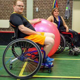 Bild från en sporthall, i förgrunden en ung man i rullstol som håller handen på en stor rosa boll. I bakgrunden en ung kvinna i rullstol.