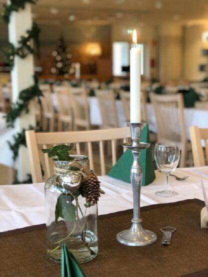 Ett tänt stearinljus och en julinspirerad bordsdekoration. I bakgrunden julpyntad restaurangmiljö.