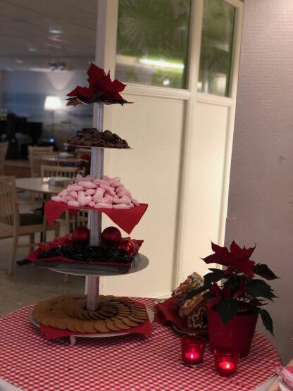 Ett fat med flera våningar fyllt av julgodis och kakor. Bredvid står en julstjärna och juldekorationer.