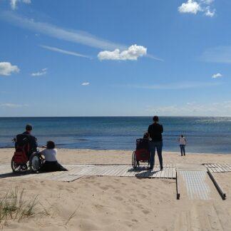 Utsikt från ut mot havet från en strand. På himlen några lätta moln och på stranden står några personer vända mot havet.
