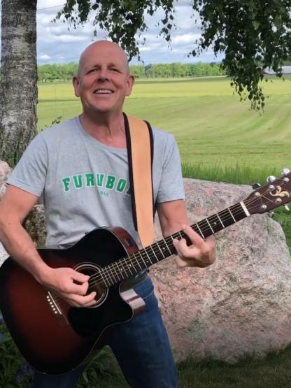"""En glad man med gitarr och en grå t-shirt med texten """"Furuboda"""""""